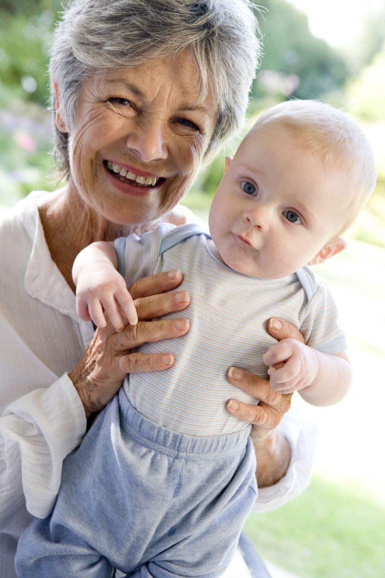 Grandmother outdoors holding grandchild