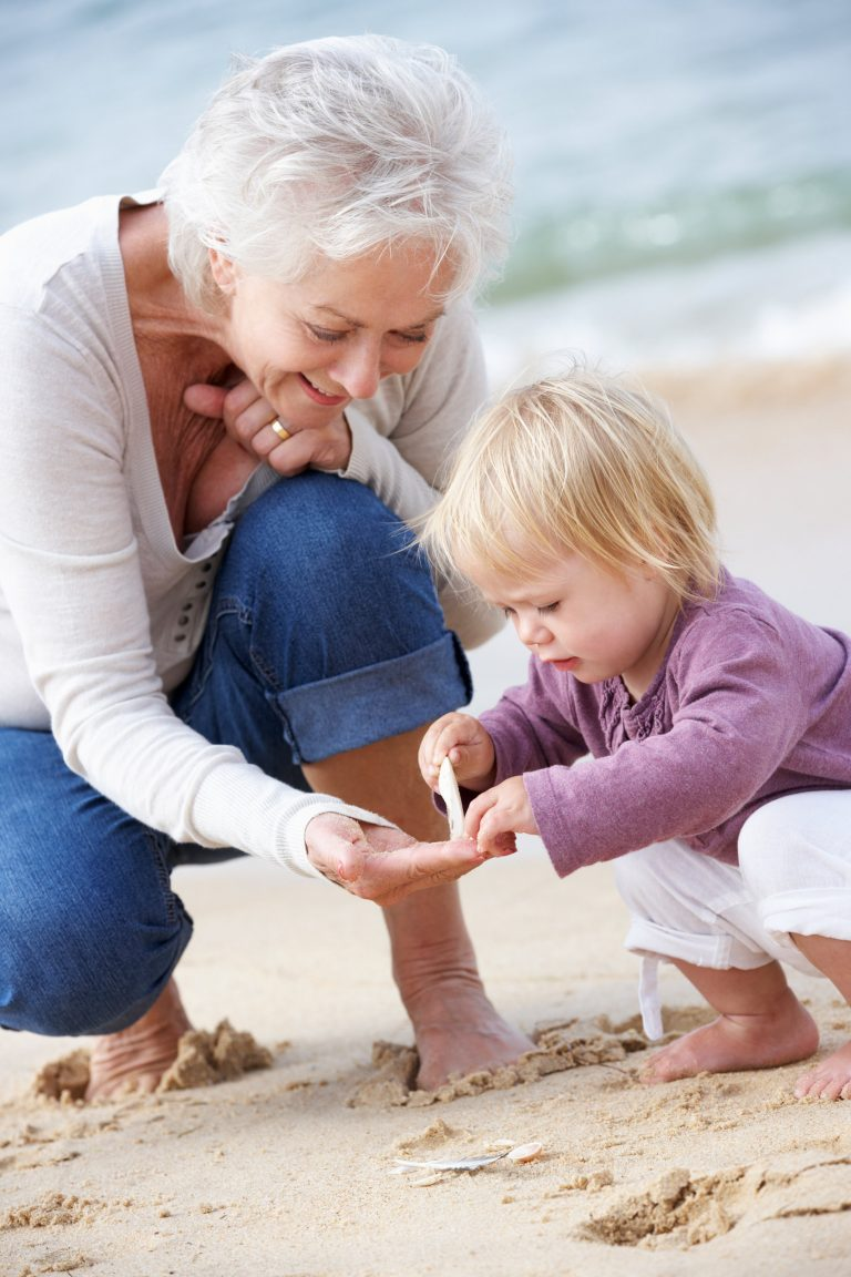 Grandmother and granddaughter spending time together on the beach.