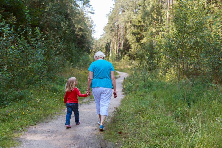 Grandma walking with grandchild in nature